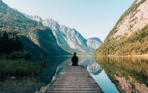 man-sitting-dock-mountains 3
